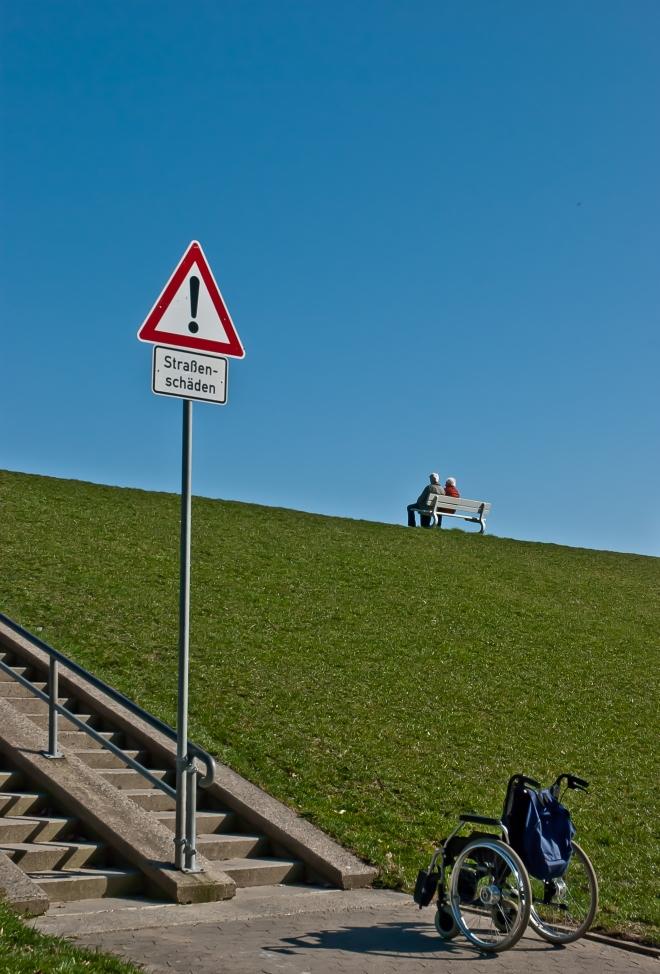 Auf dem Bild ist im Vordergrund ein leerer Rollstuhl zu erkennen. Daneben steht ein Schild neben einem Treppenaufgang, auf dem steht: Achtung Straßenschäden. Weiter oben auf eine Art Damm ist ein Paar auf einer Bank zu erkennen