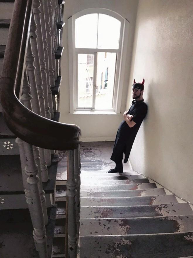 Steven steht im schwarzen Kleid und Teufelsohren auf