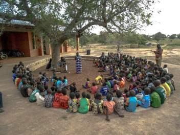 Ein Märchenabend im Operndorf Afrika. Kinder sitzen im Kreis. In dessen Mitte steht eine Sängerin