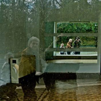 Eine Zweifachspiegelung: Steven im Schaufenster sowie Spiegeln einer Wand. Links von Steven ein Ehepaar mit Fahrrad