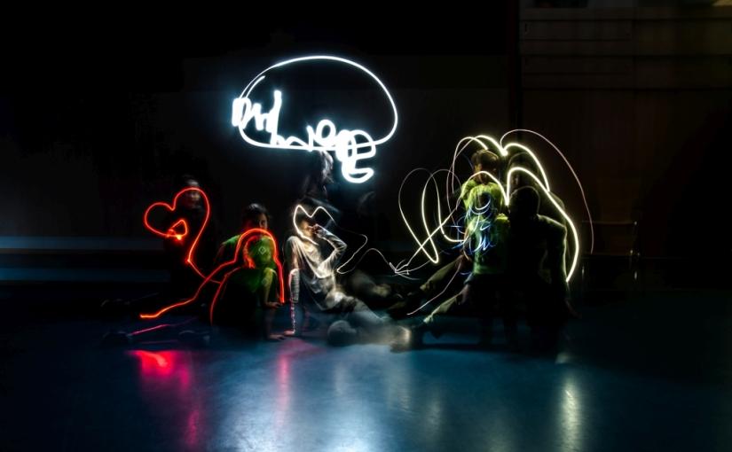 Das Foto zeigt Steven mit vier Kindern in einem dunkeln Raum wie sie mit Licht malen.